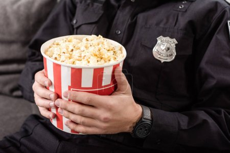 cropped view of policeman sitting on couch with striped popcorn bucket