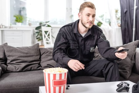 man in police uniform sitting on couch and watching movie