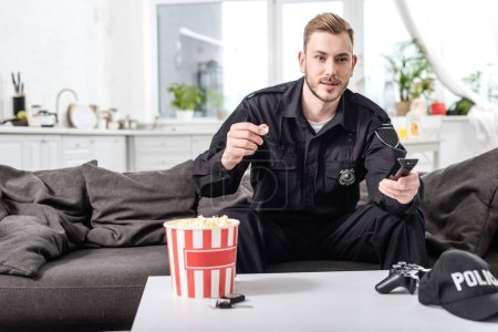 policeman sitting on couch, eating popcorn and watching movie