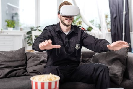 police officer with virtual reality headset on head sitting on couch and playing video game