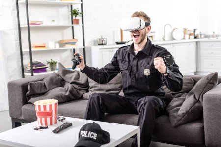policeman with virtual reality headset on head playing video game and screaming with joy on couch