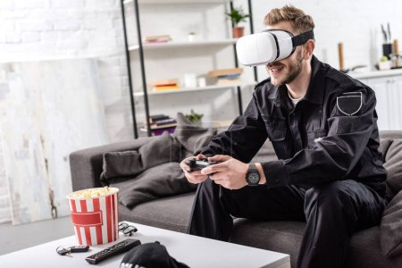 Photo for Policeman with virtual reality headset on head holding gamepad, sitting on couch and playing video game - Royalty Free Image