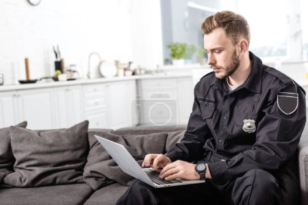 handsome police officer sitting on couch and typing on laptop keyboard