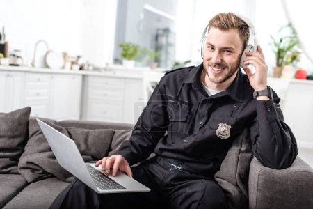 Handsome policeman sitting on sofa with laptop and listening to music
