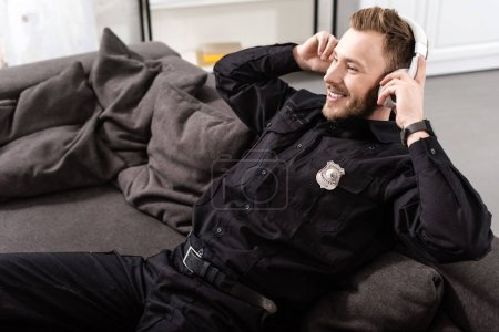 Smiling policeman sitting on couch and putting on headphones