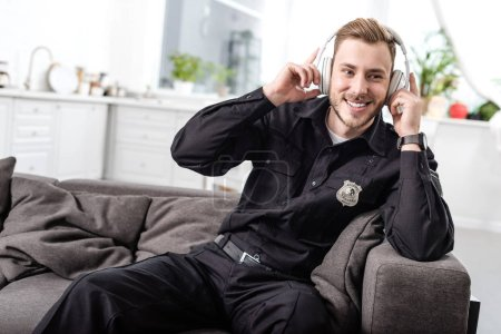 Smiling police officer sitting on couch and listening to music with headphones