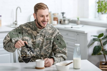 Handsome man in military uniform smiling and pouring coffee in cup from kettle at kitchen table