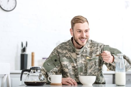 Smiling man in military uniform eating cornflakes at kitchen