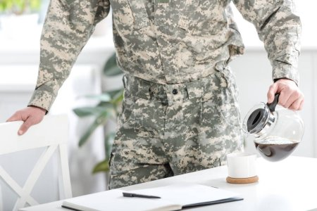 crooped view of army soldier pouring filtered coffee in kitchen