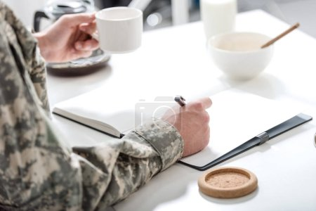 cropped view of army soldier sitting at kitchen table, writing and having breakfast