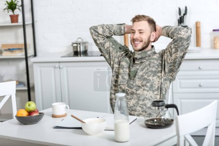 smiling army soldier sitting at kitchen table with hands on head while having breakfast