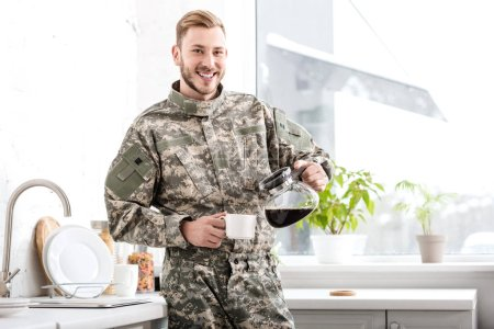 smiling army soldier pouring filtered coffee in kitchen