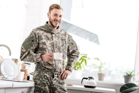 smiling army soldier holding cup of coffee in kitchen
