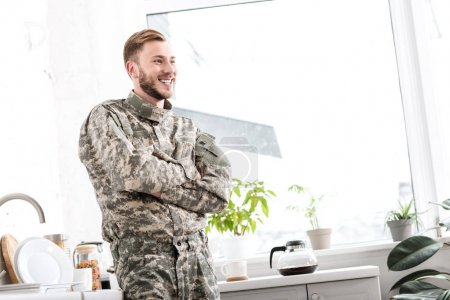 smiling army soldier with arms crossed in kitchen