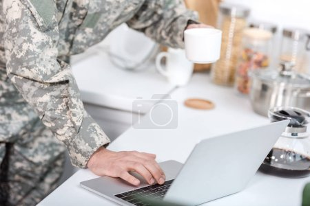 Photo for Cropped view of soldier holding cup of coffee and using laptop at kitchen - Royalty Free Image