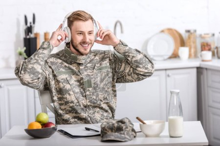 handsome army soldier in headphones sitting at kitchen table during breakfast at home