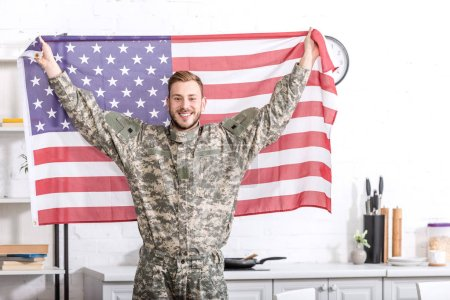 handsome army soldier standing, looking at camera and proudly holding american flag