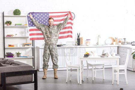 smiling army soldier standing, looking at camera and proudly holding american flag in kitchen