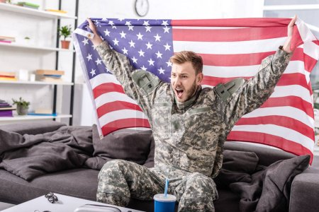 excited army soldier sitting on couch, cheering and proudly holding american flag