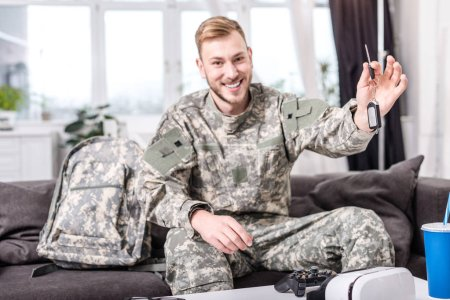 excited army soldier sitting on couch at home, looking at camera and holding key