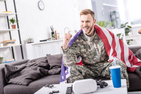 excited army soldier covered in american flag sitting on couch, cheering and and watching football match at home