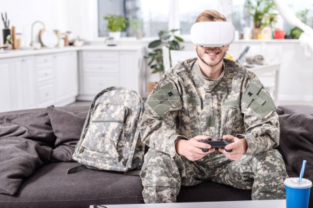 smiling army soldier in virtual reality headset playing video game on couch