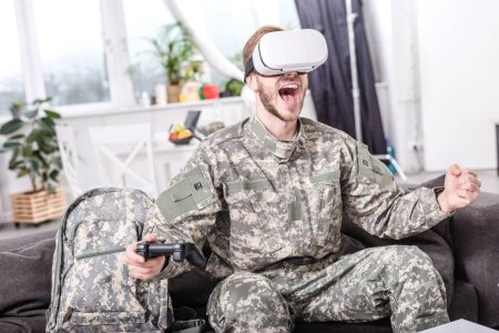Photo for Excited soldier in virtual reality headset playing video game on couch - Royalty Free Image