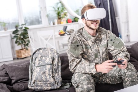 smiling soldier in virtual reality headset playing video game on couch