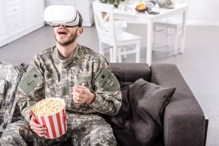 Photo for Excited soldier in virtual reality headset sitting on couch and eating popcorn - Royalty Free Image