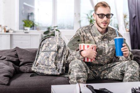 Photo pour Beau soldat à lunettes 3d sur le canapé à regarder le film avec pop corn et eau gazeuse - image libre de droit