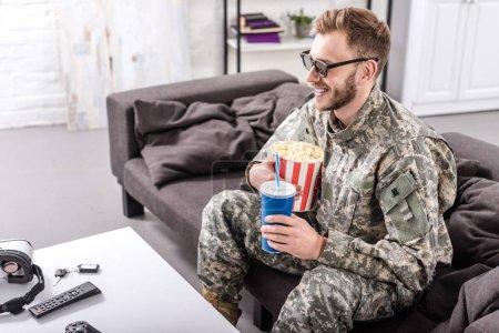 Photo pour Sourire de soldat de l'armée dans les lunettes 3d sur le canapé à regarder le film avec pop corn et eau gazeuse - image libre de droit