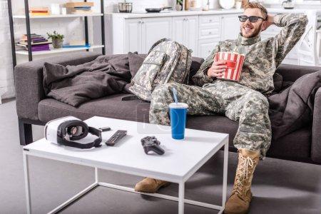 Photo pour Soldat de l'armée en uniforme militaire portant des lunettes 3d, manger des pop corn et regarder film sur canapé - image libre de droit
