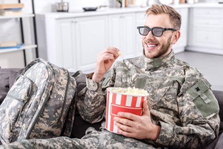 smiling soldier in military uniform wearing 3d glasses, eating popcorn and watching movie on couch