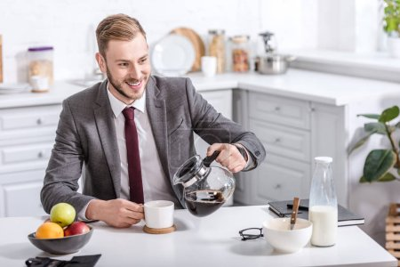 handsome businessman pouring filtered coffee in cup at kitchen table