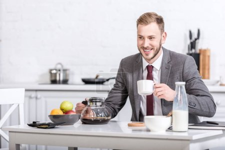 smiling businessman drinking coffee at kitchen table