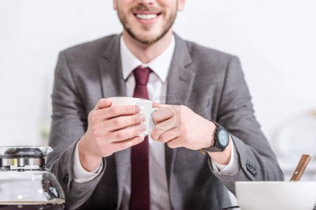 cropped view of smiling businessman drinking coffee in kitchen