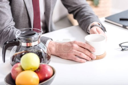 cropped view of businessman drinking coffee in kitchen