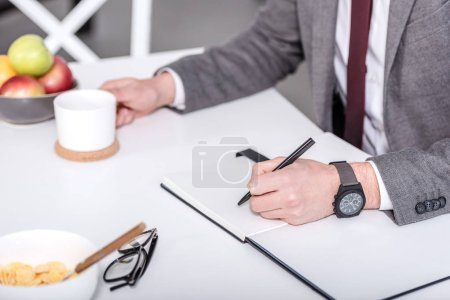 cropped view of businessman writing in notebook with pen while having breakfast