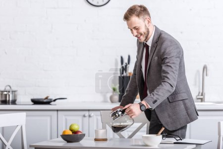 smiling businessman pouring filtered coffee in cup at kitchen