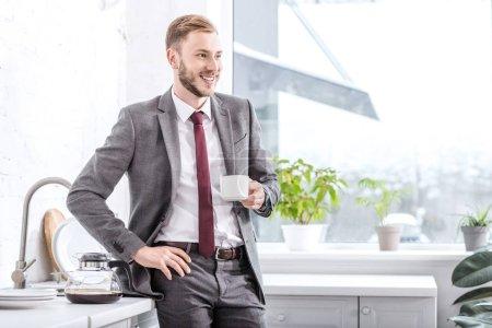 Photo pour Bel homme d'affaires buvant du café dans la cuisine à la maison - image libre de droit