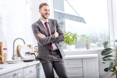 smiling businessman with crossed arms in kitchen