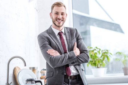 smiling businessman with crossed arms in kitchen looking at camera