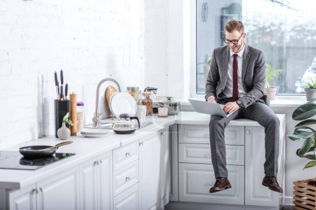 businessman working on laptop in kitchen at home