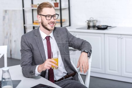 businessman in glasses sitting at kitchen table, drinking orange juice and looking away