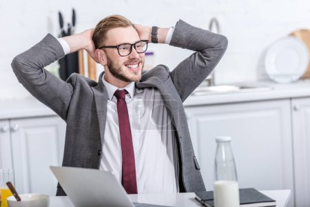 Photo for Smiling businessman with hands on head sitting at kitchen table and using laptop during breakfast - Royalty Free Image