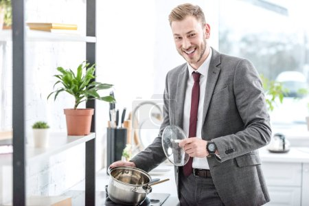 smiling businessman in formal wear holding pot and getting ready to cook in kitchen