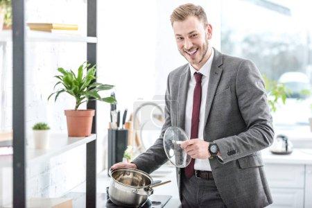 Photo pour Homme d'affaires souriant dans les vêtements formels tenant le pot et s'apprête à faire cuire dans la cuisine - image libre de droit