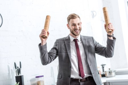 excited businessman holding pepper pots and getting ready to cook in kitchen