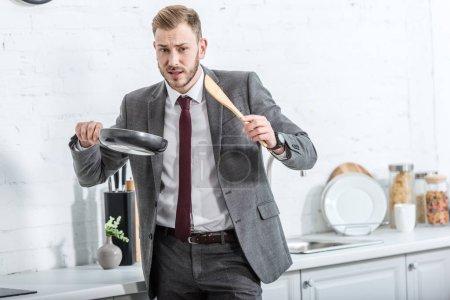 Photo pour Homme d'affaires confus dans les vêtements formels tenant la spatule avec pan et s'apprête à faire cuire dans la cuisine - image libre de droit