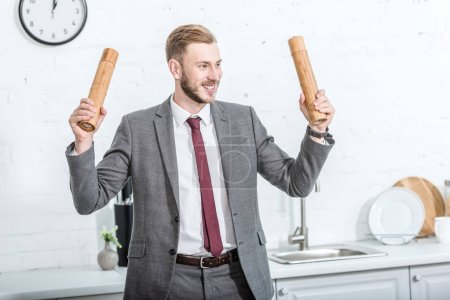 smiling excited businessman holding pepper pots and getting ready to cook in kitchen